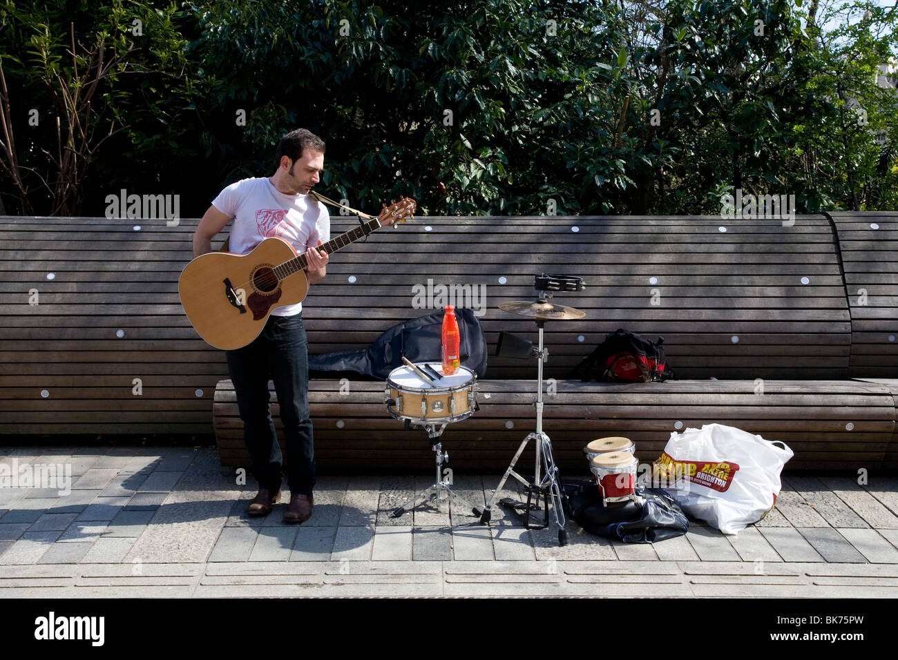 A busker with a guitar stands next to his drum and high hat next to the Dome and  Pavilion gardens in Brighton. - Stock Image