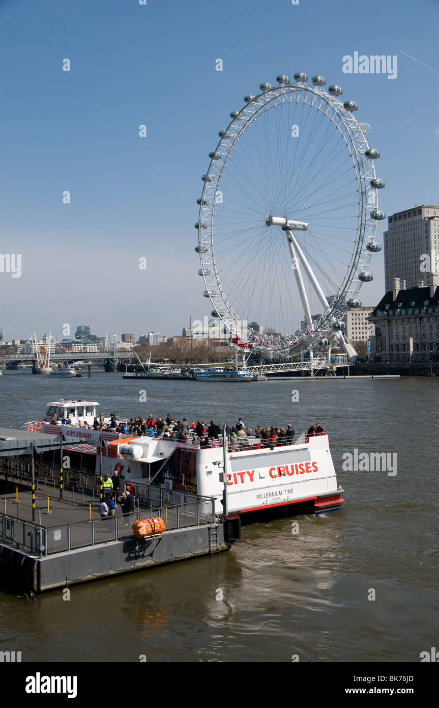 tourists board a River Thames cruise ship with the London Eye in the background - Stock Image