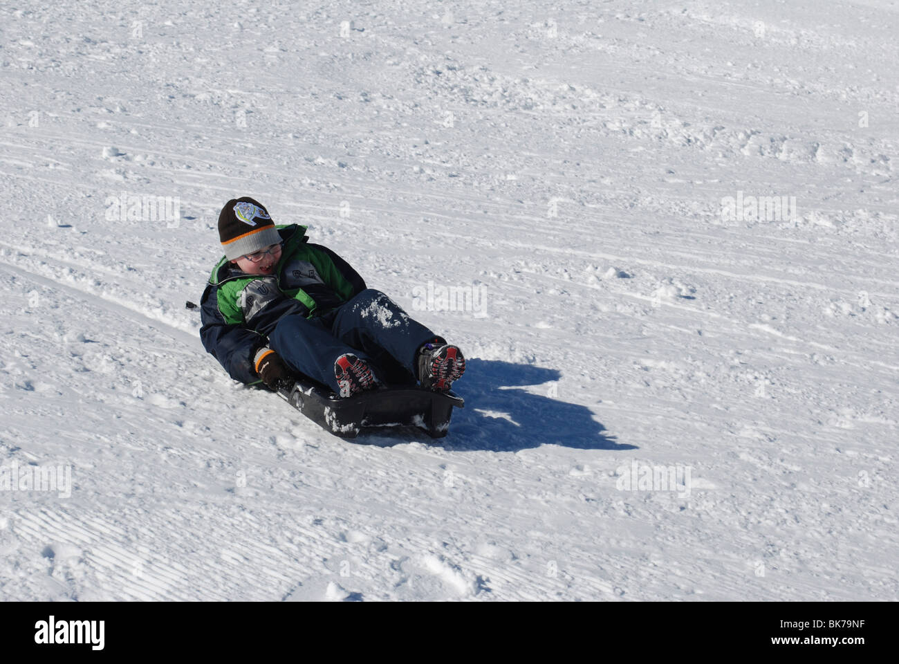 Boy of 7 slides down the snowy slopes on a sleigh view from front - Stock Image