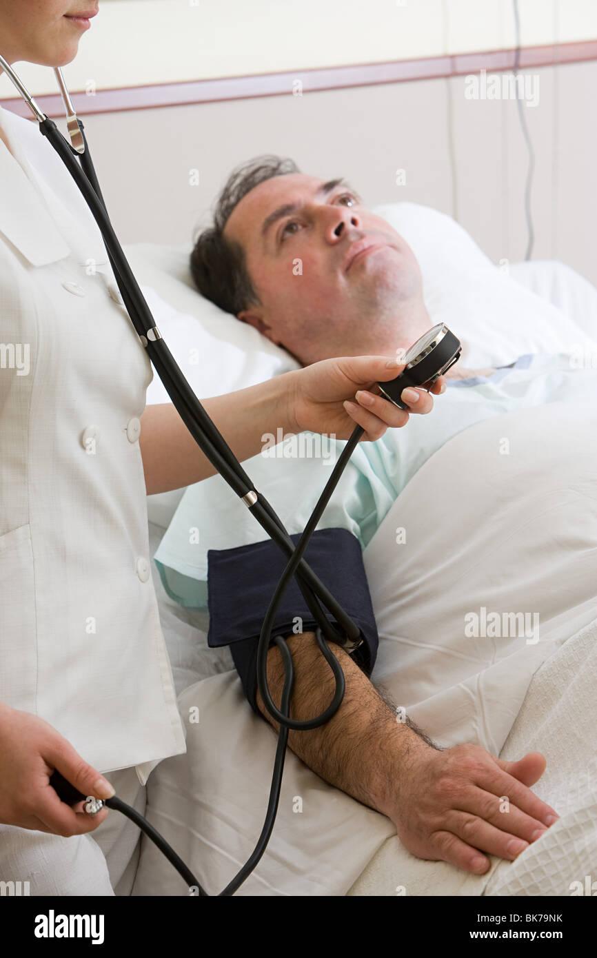 Nurse using blood pressure gauge on patient - Stock Image
