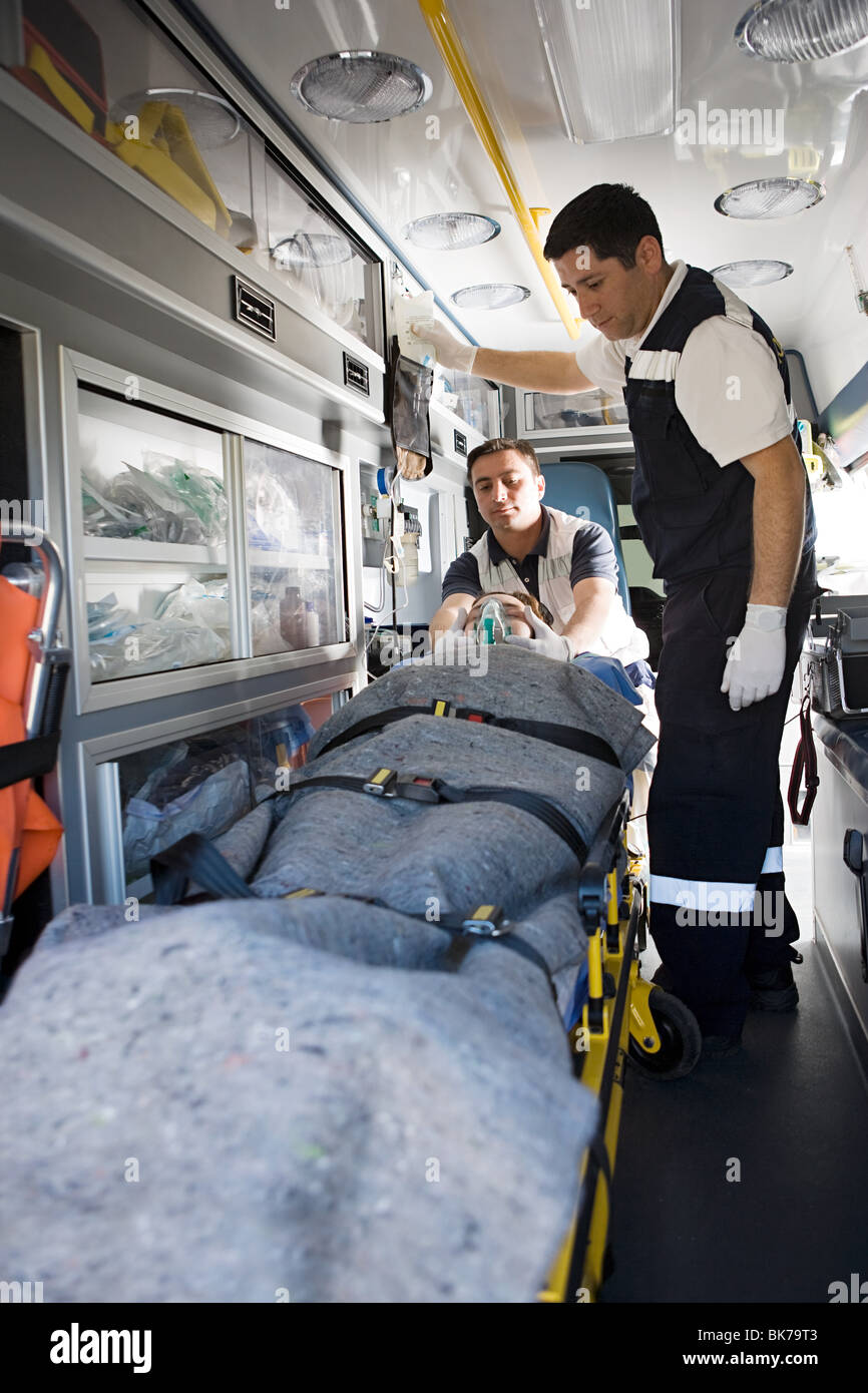 Ambulance staff and patient on stretcher Stock Photo