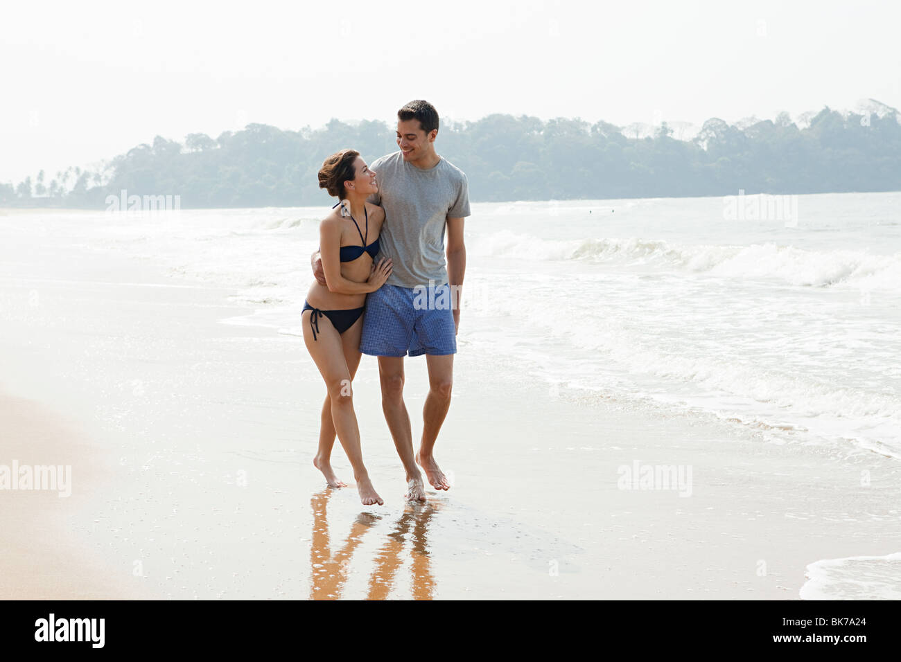 Couple walking by the ocean - Stock Image