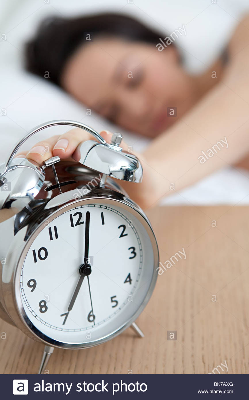 Woman reaching out for alarm clock Stock Photo