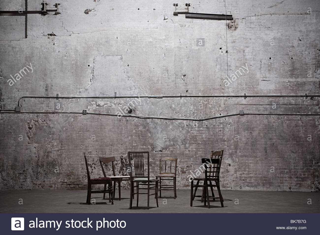 Chairs in empty warehouse - Stock Image
