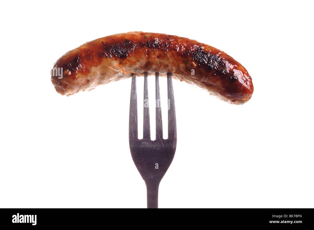 Cooked Sausage on fork - Stock Image