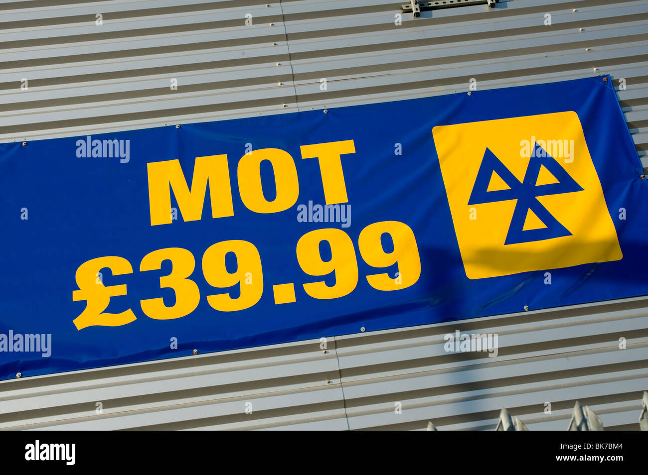 Sign showing cost to mot a vehicle on the side of a building in England - Stock Image