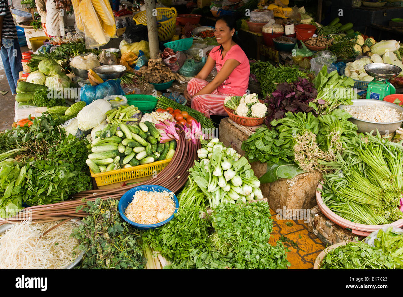 Young woman sitting in her vegetable stall in the daily market in the Vietnam Mekong Delta town of Ha Tien - Stock Image