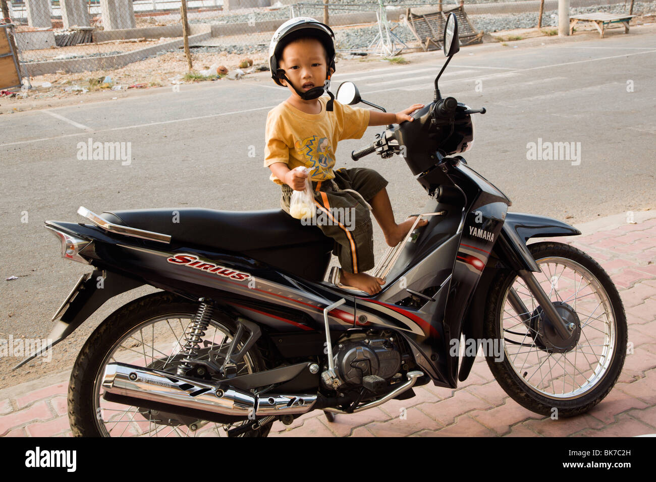 Very young motorbikedriver waiting for mummy by the daily market in Ha Tien Mekong Delta Vietnam - Stock Image