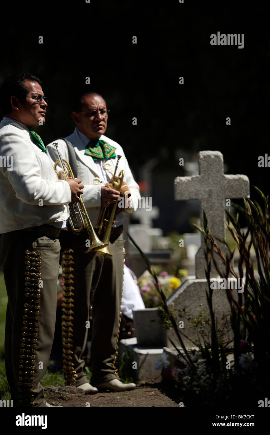 Mariachis stand by a grave at the Dolores cemetery in Mexico City - Stock Image