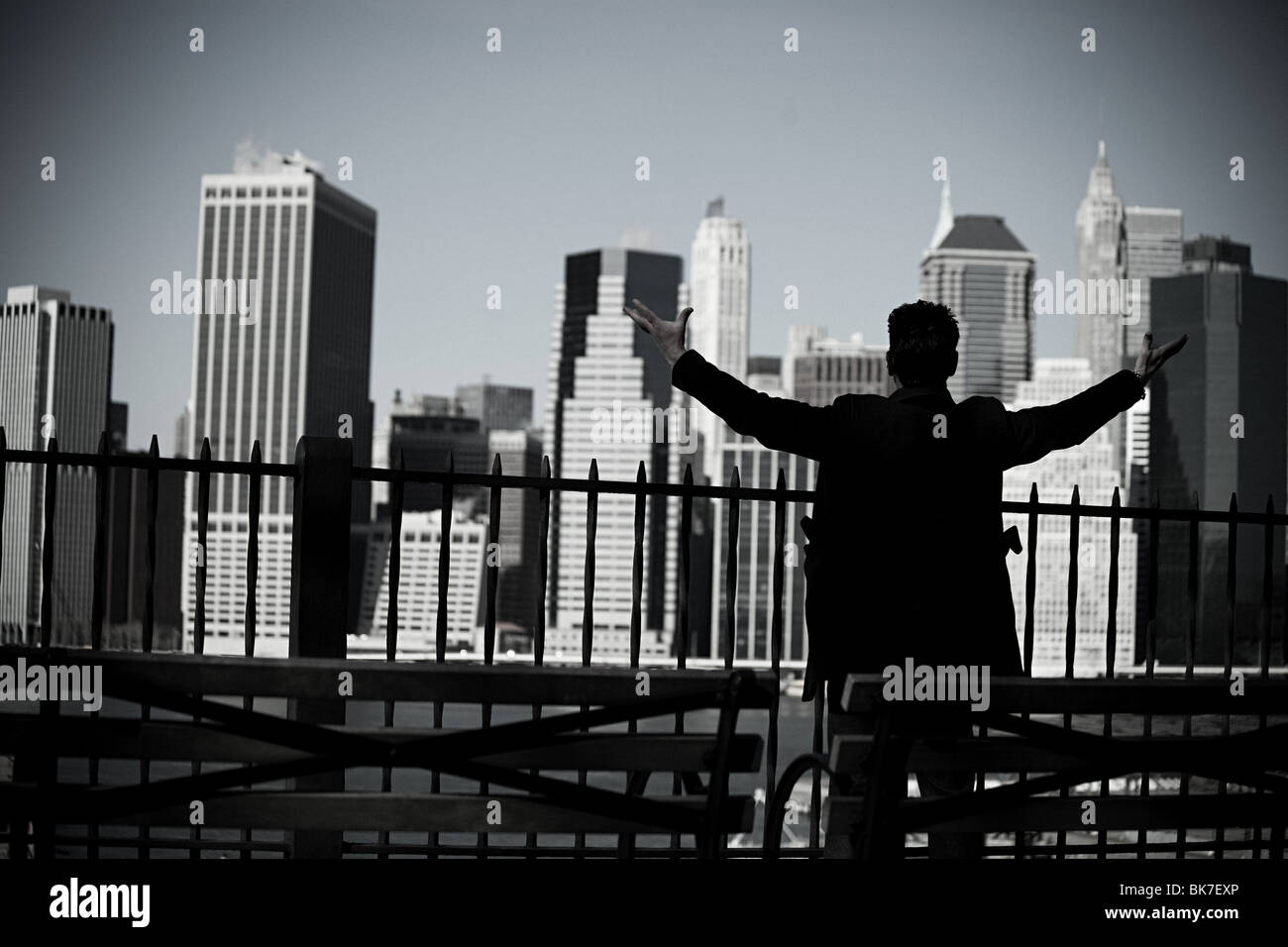 Man with arms open and view of lower manhattan Stock Photo