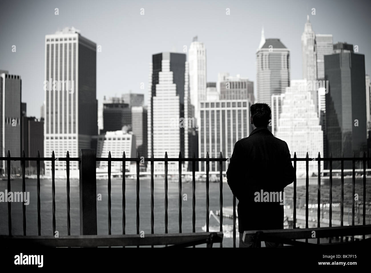 Man looking to lower manhattan from brooklyn heights promenade - Stock Image