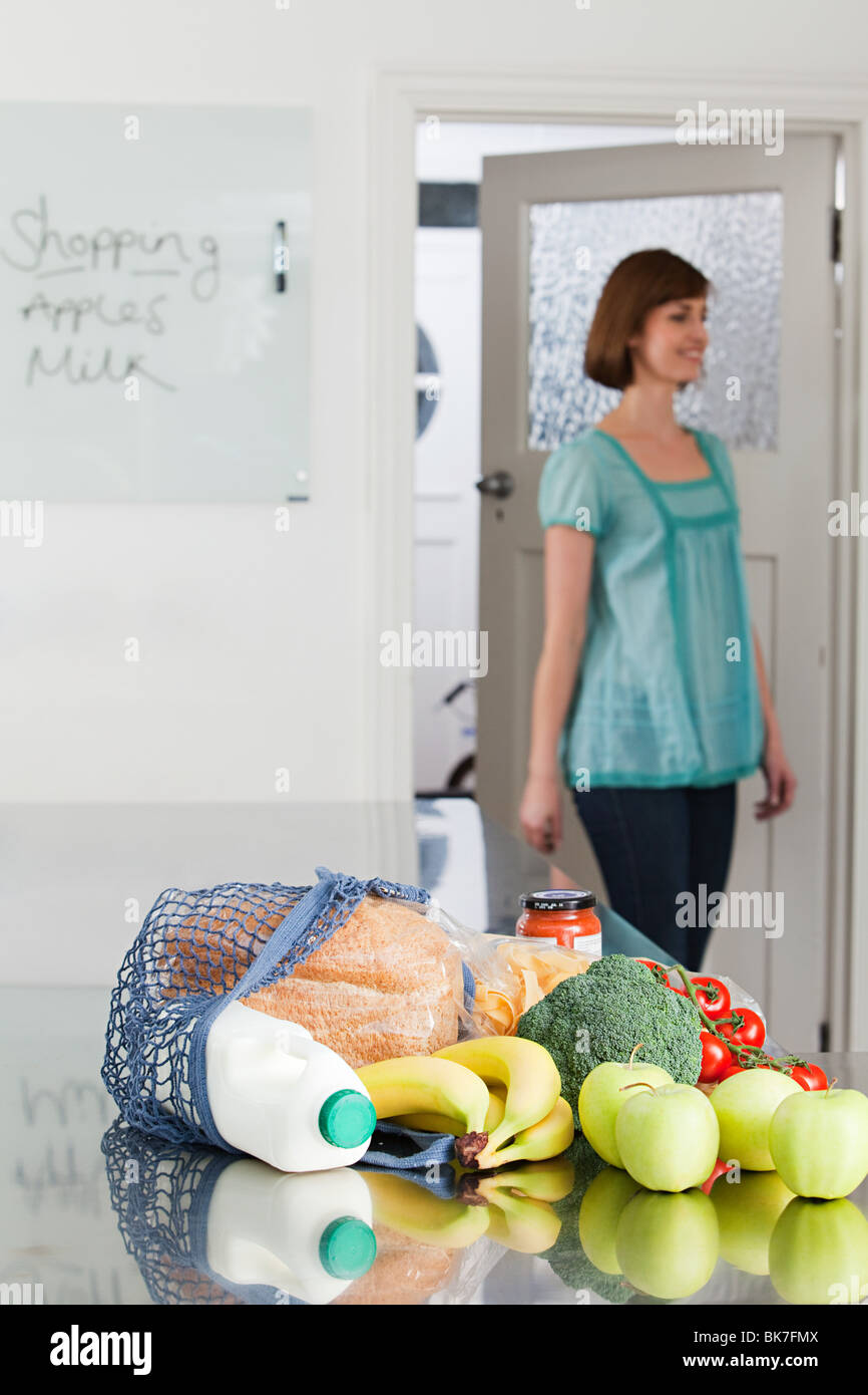 Woman and groceries in kitchen - Stock Image