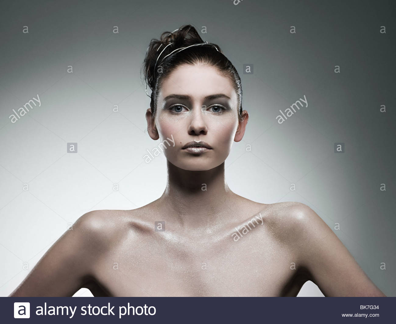 Young woman covered with silver make up - Stock Image
