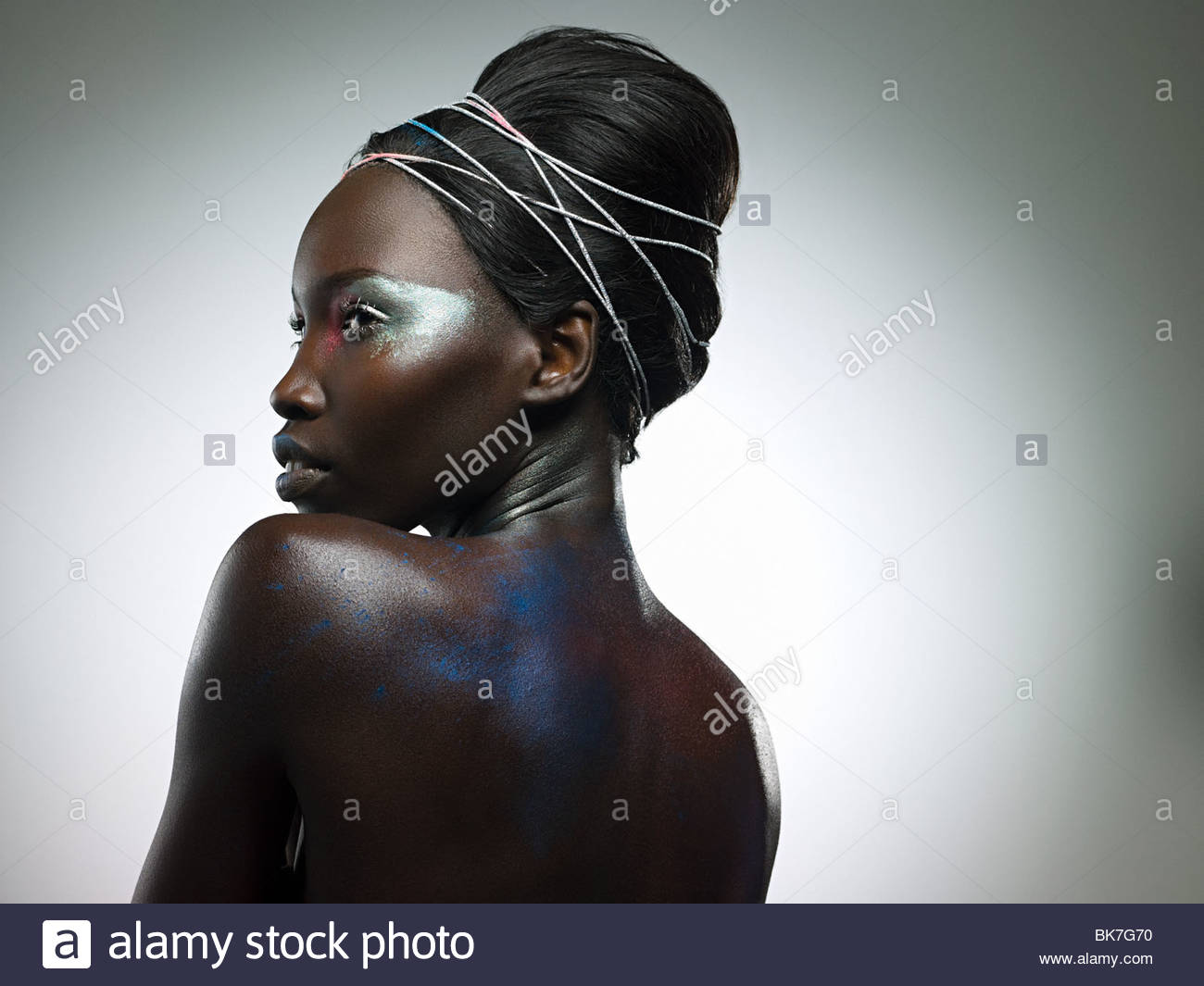 Young woman covered in metallic make up - Stock Image