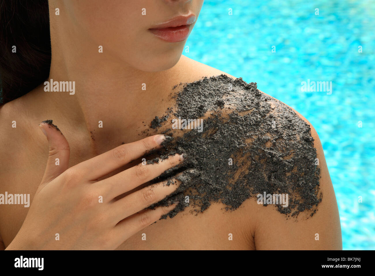 Applying sesame scrub treatment by the pool&#10, - Stock Image