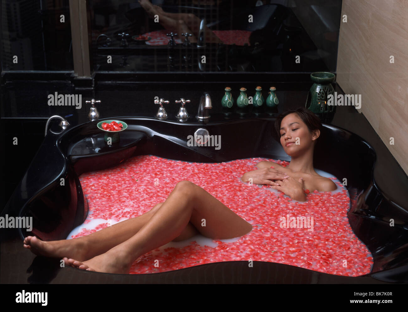 Young woman relaxing in a flower bath - Stock Image