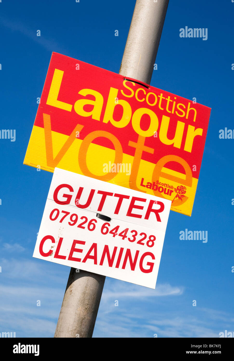 An amusing Labour 2010 election poster on a lamppost above another sign for gutter cleaning. - Stock Image
