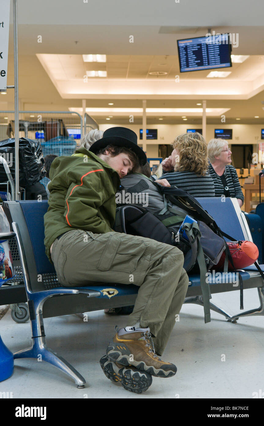 Man sleeping on an airport seat while is flight is canceled - Stock Image