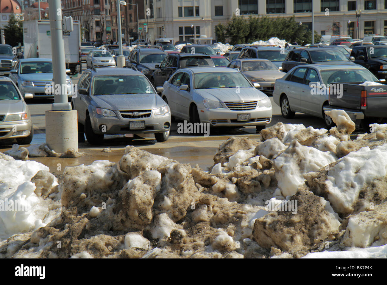 Washington DC 10th Street NW dirty grimy snow plowed ice thawing melting wet pollution winter cold weather parking - Stock Image