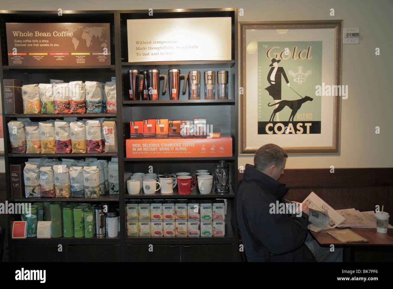 Washington DC Metro Center Starbucks store business company coffee shop packaging mugs merchandise caffeine man - Stock Image
