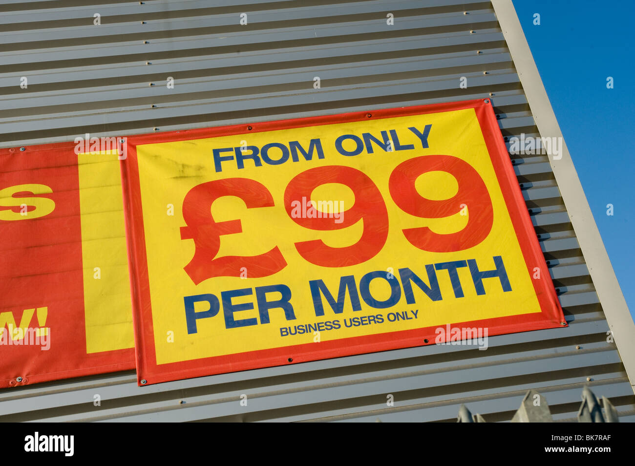 Sign showing cost to hire a vehicle on the side of a building in England - Stock Image