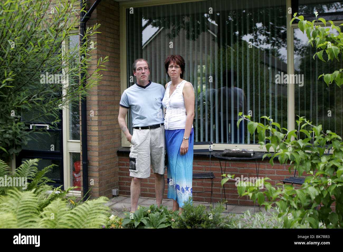 Couple in front of their house, married couple serious faces - Stock Image