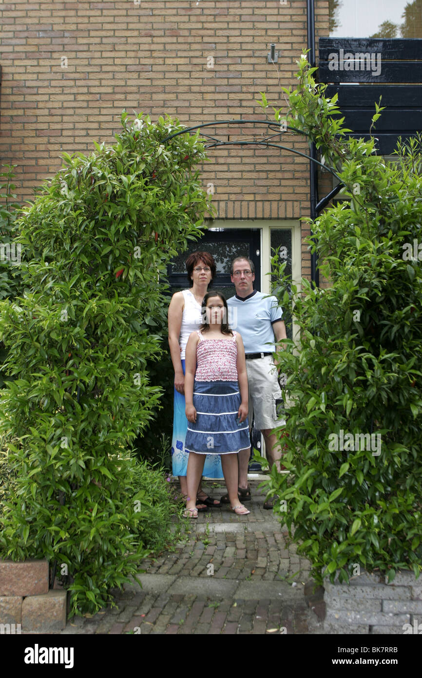 Middle class family in front of house - Stock Image