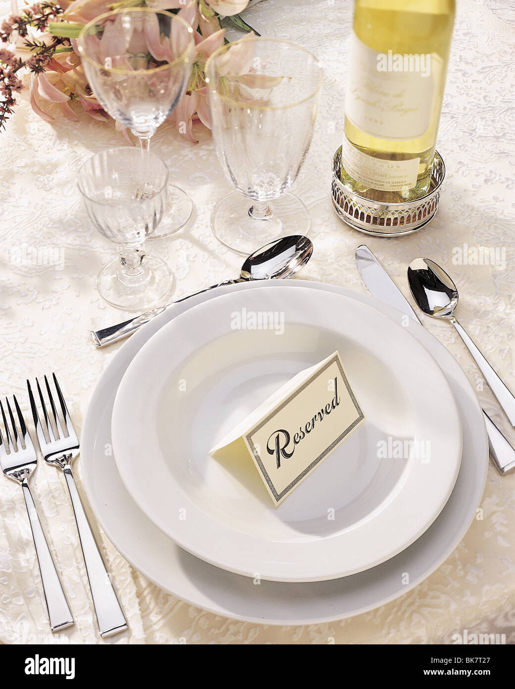 Reserved card on a place setting with crystal, flatware and flowers on elegant brocade cloth. - Stock Image