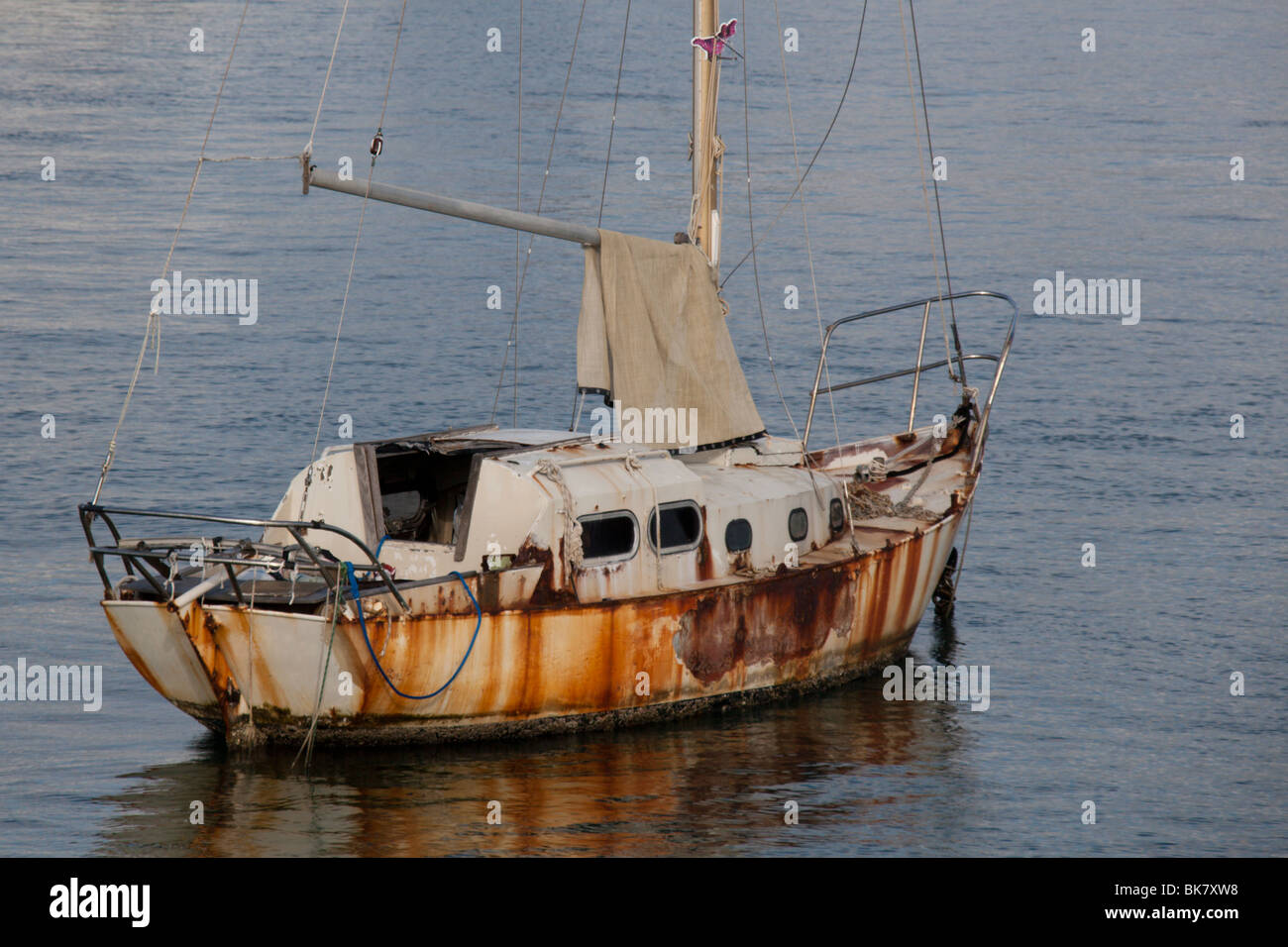 An neglected sailing boat sits at anchor on the Intracoastal waterway,Palm Beach, Florida Stock Photo