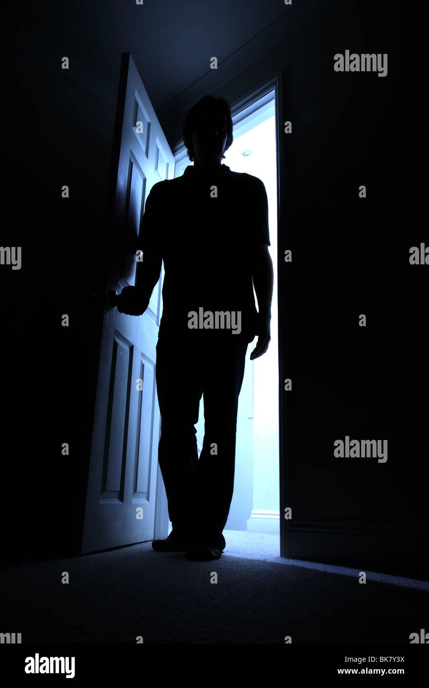 Silhouette of a male entering a dark room with a shaft of light behind - Stock Image