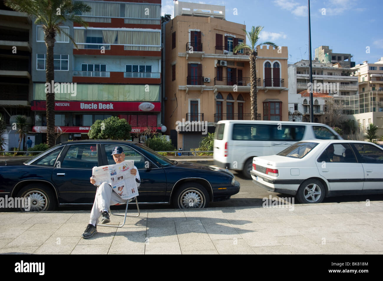 A resident of Beirut read the latest news on the cornice of Beirut Lebanon - Stock Image
