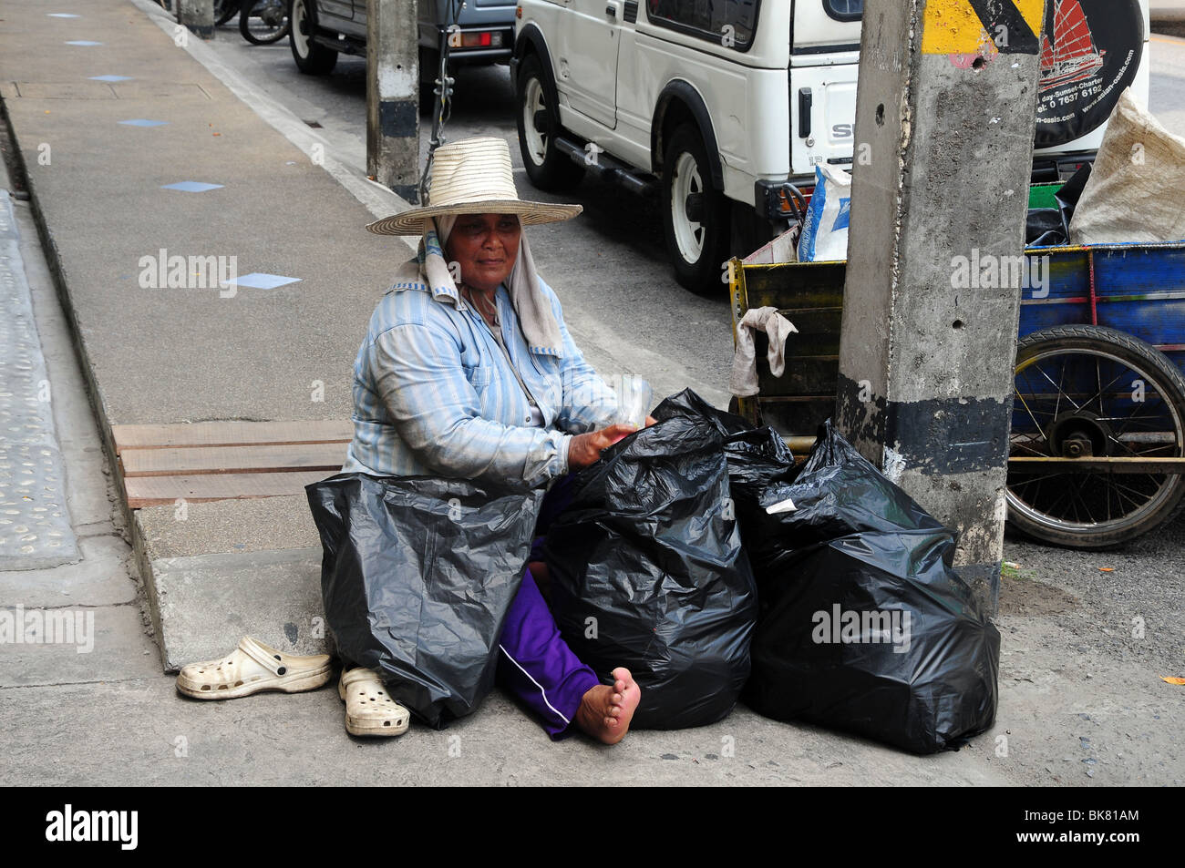 Poor person in Thailand sifting through rubbish - Stock Image
