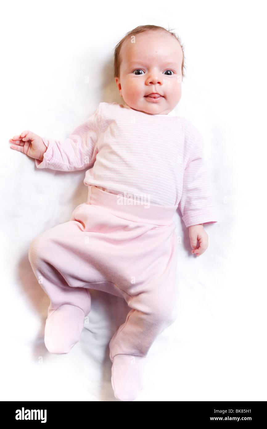 The baby lies on white bedsheet. - Stock Image
