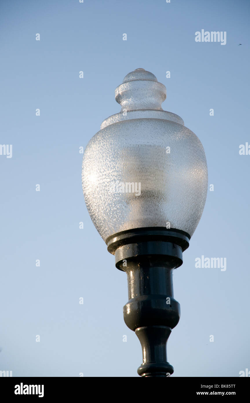 Glass lamppost  against a blue sky - Stock Image