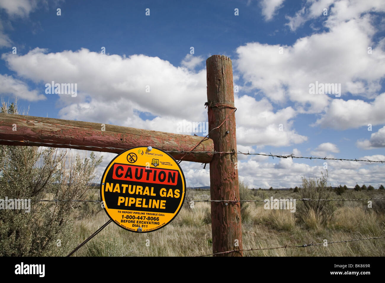A caution sign on a barbed wire fence warns visitors about a Trans Canada Natural gas pipeline buried nearby, near - Stock Image
