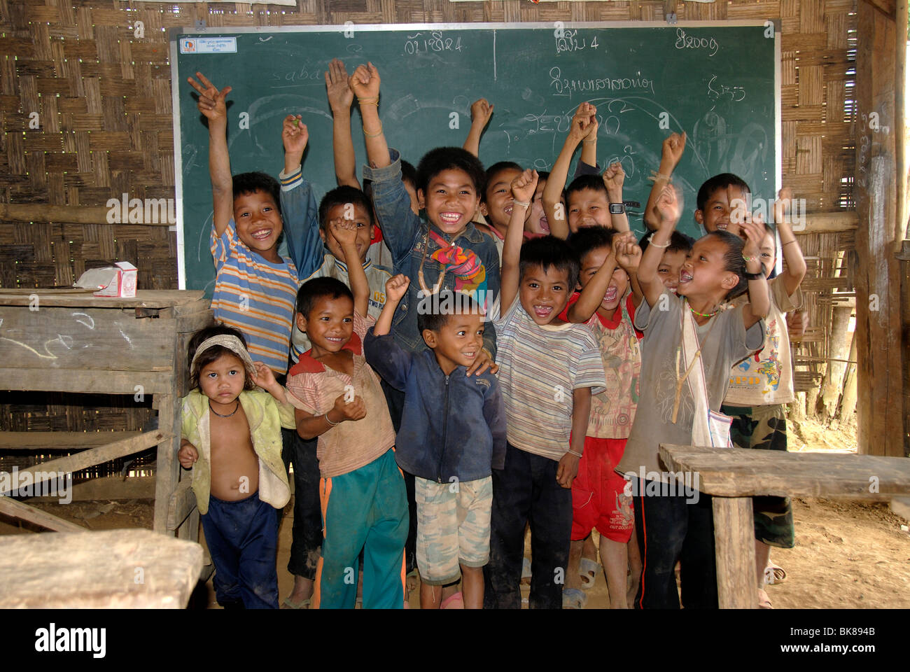 Poverty, developing country, education, primary school, pleasure, students stretching their hands up in front of - Stock Image