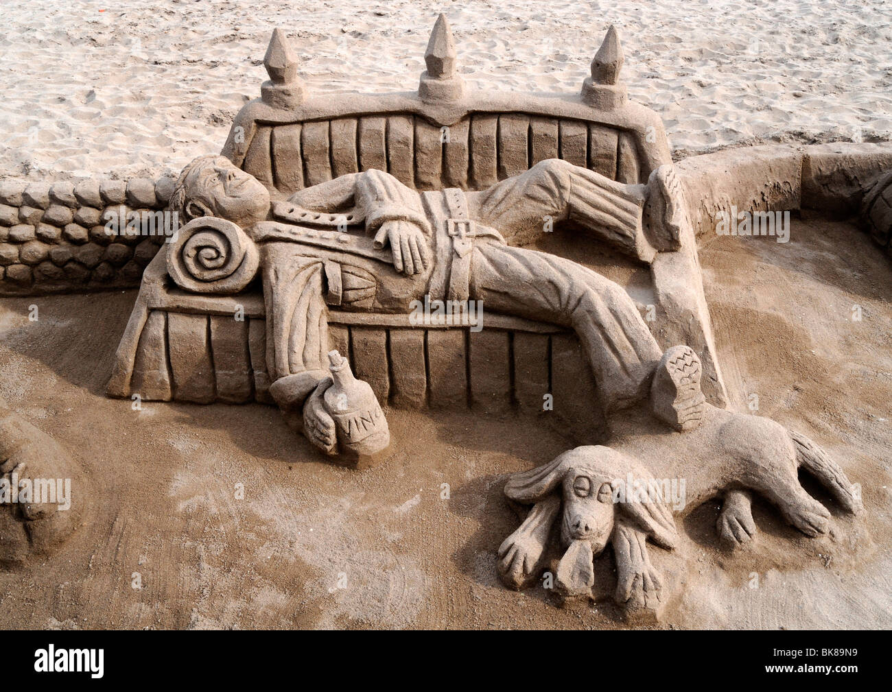 Sand sculpture of a tramp with a dog lying on a bench - Stock Image