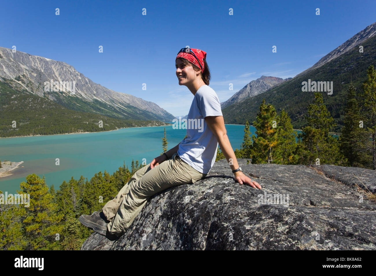 Young woman, hiker, backpacker sitting on rock, resting, enjoying panorama over Lake Bennett, historic Chilkoot Stock Photo