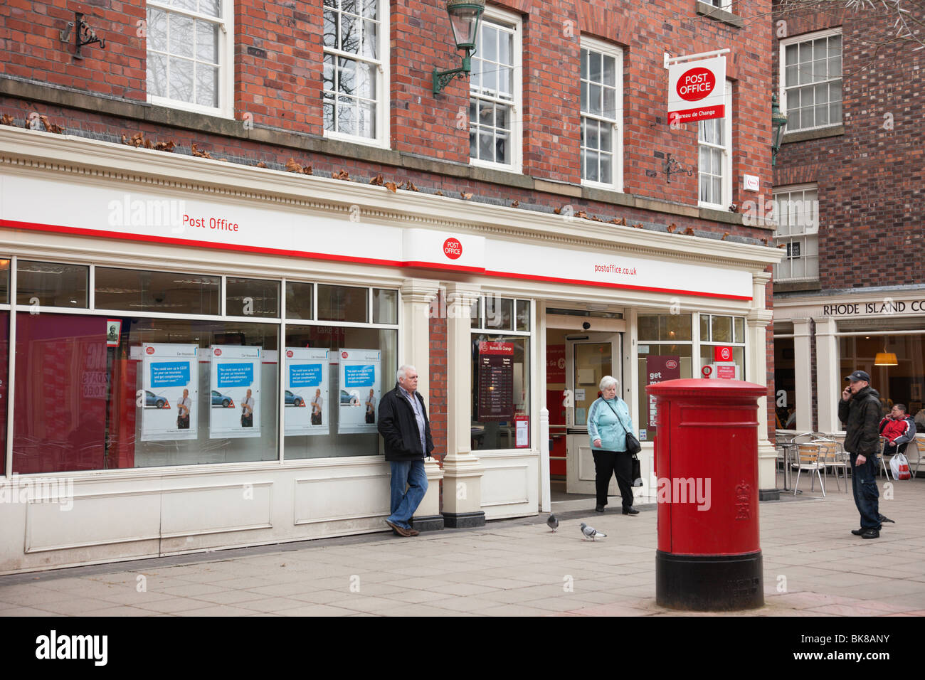Street scene outside a Post Office with postbox with people. Warrington, Cheshire, England, UK. - Stock Image