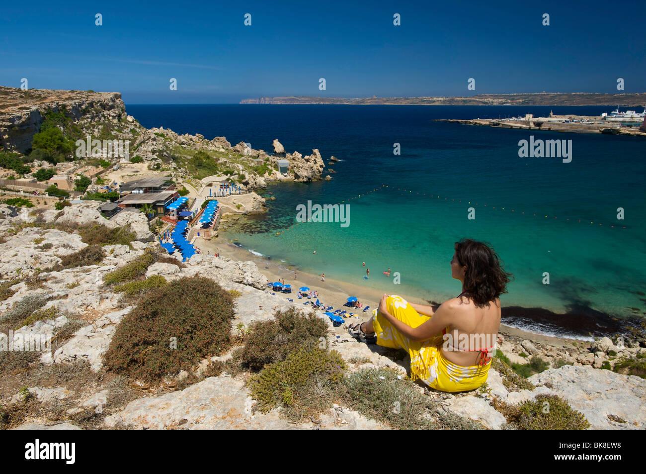 Woman looking on Paradise Bay in Cirkewwa, Malta, Europe - Stock Image