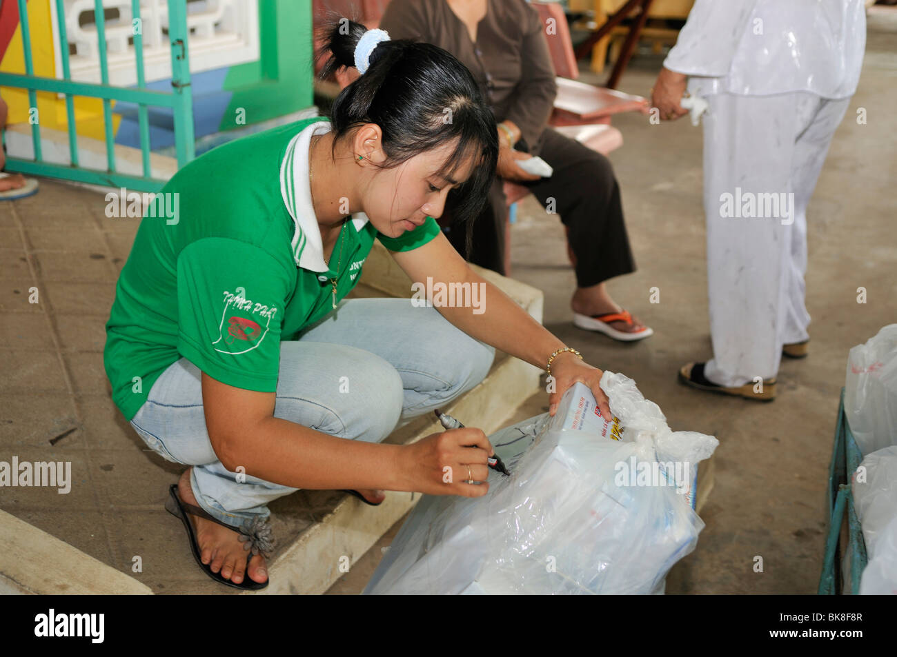 Sales clerk labelling a pack of fish sauce Nuoc Mam, Phu Quoc, Vietnam, Asia - Stock Image