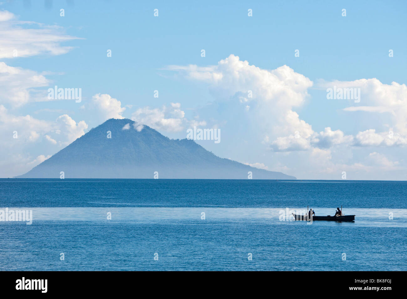 Diving boat in the Bunaken Marine Park in front of Mt Manado Tua, North Sulawesi, Indonesia - Stock Image