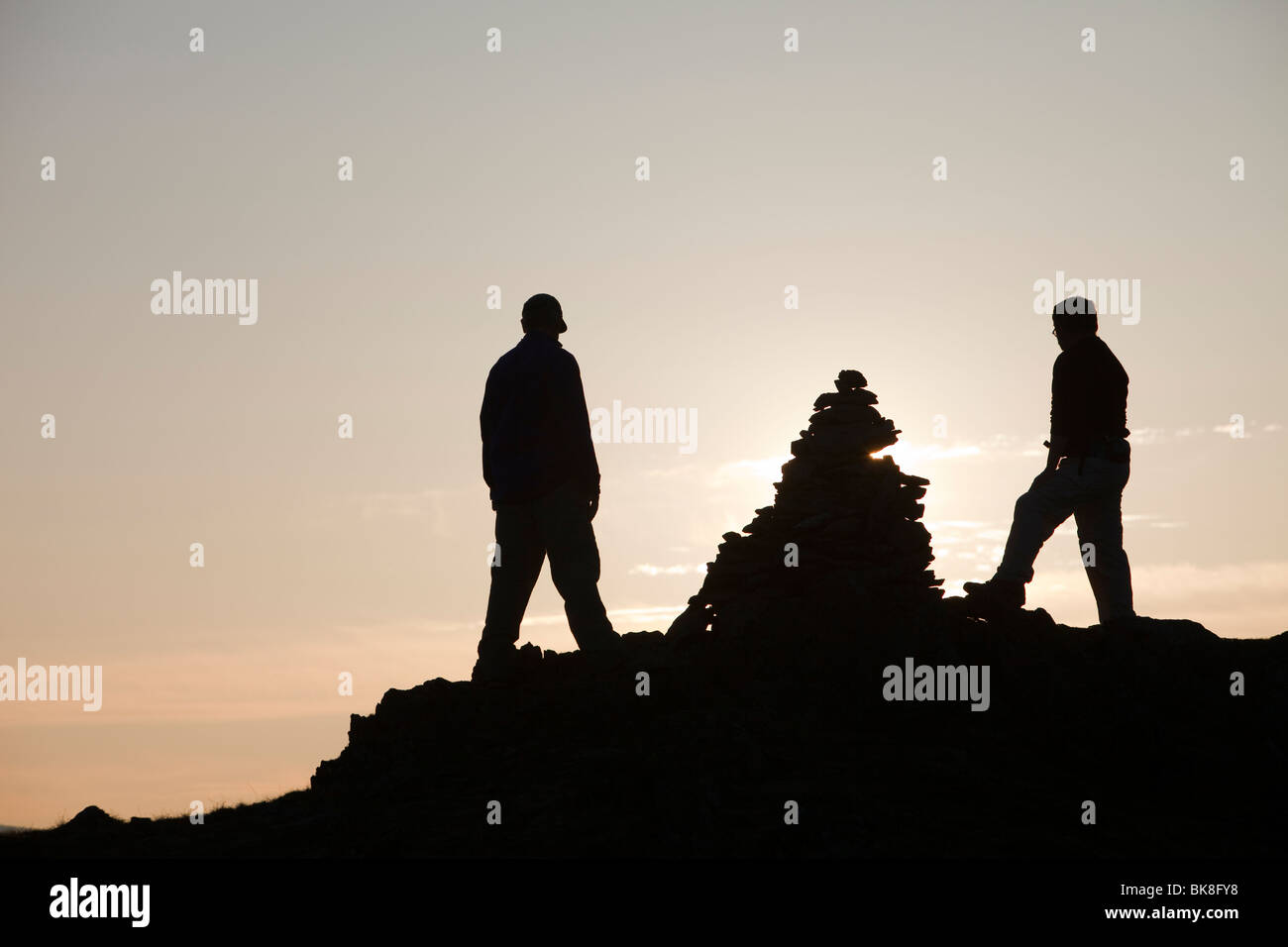 Hill walkers on Nab Scar in the Lake District, Cumbria, UK, at dusk. - Stock Image