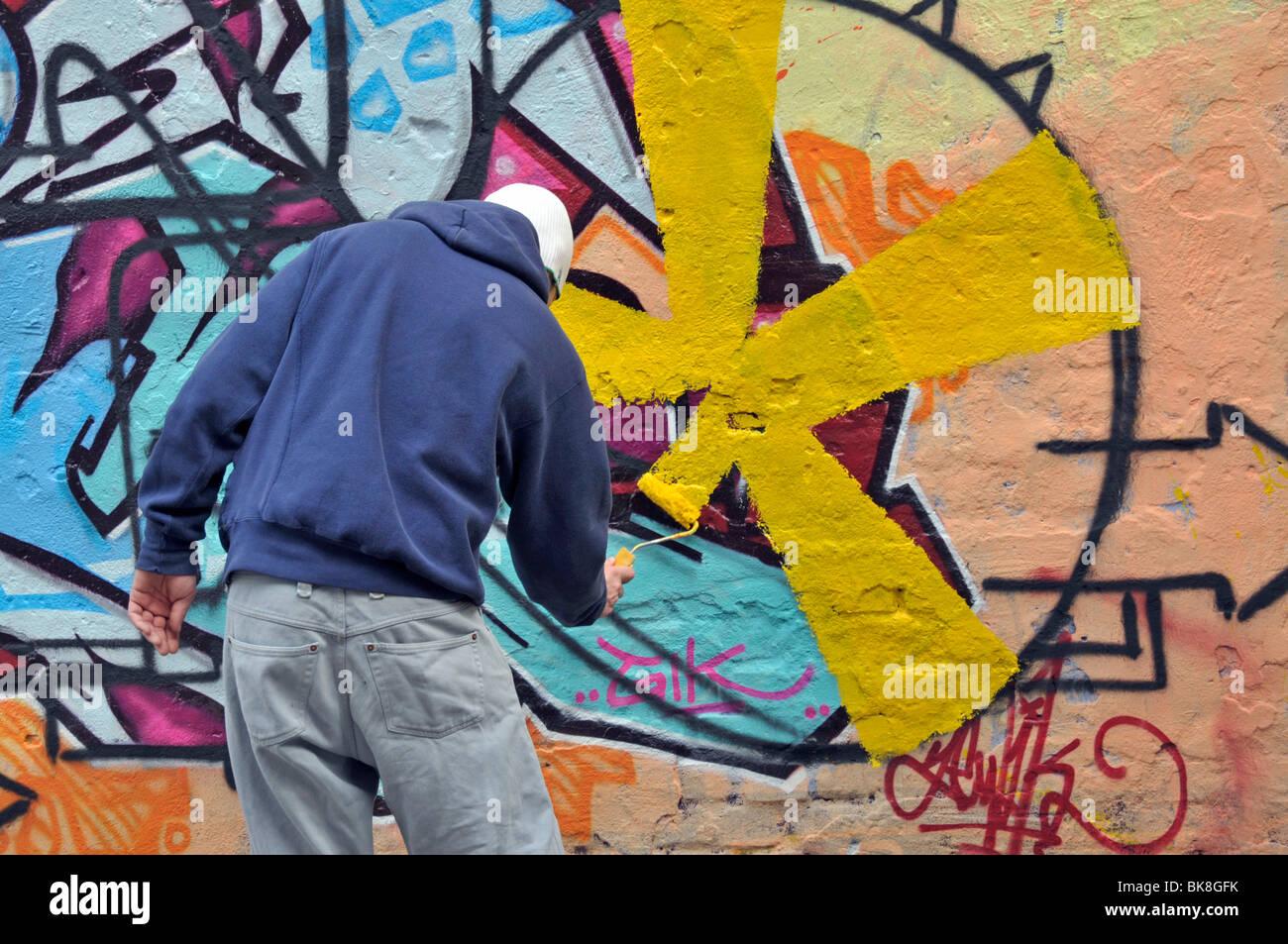 Graffiti artist working on a graffiti-covered wall, Cologne, North ...