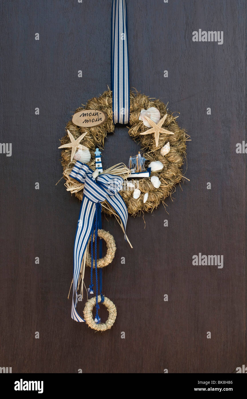 Maritime Frisian wreath on door, text: Moin moin, Frisian greeting, blue-white with starfish, lighthouse, boats - Stock Image