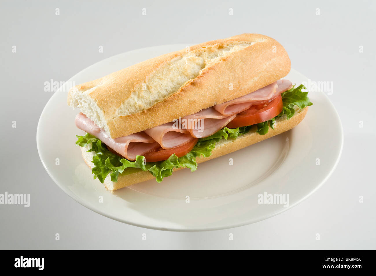 Ham and tomato sandwich on baguette - Stock Image