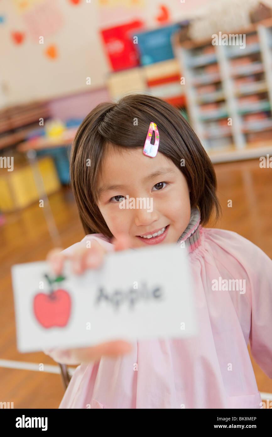 Kindergarten Girl Holding Picture Card Stock Photo