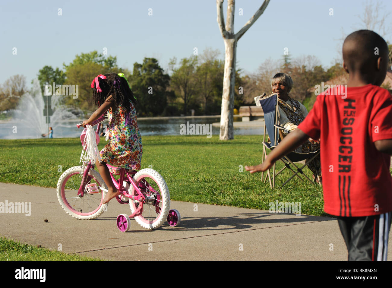 an aunt looks around after her little niece riding on a tricycle - Stock Image