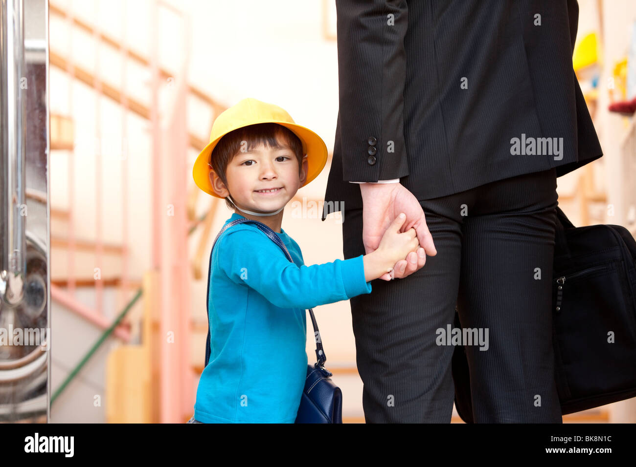 Businessman Picking Up Son from Day-care Center - Stock Image