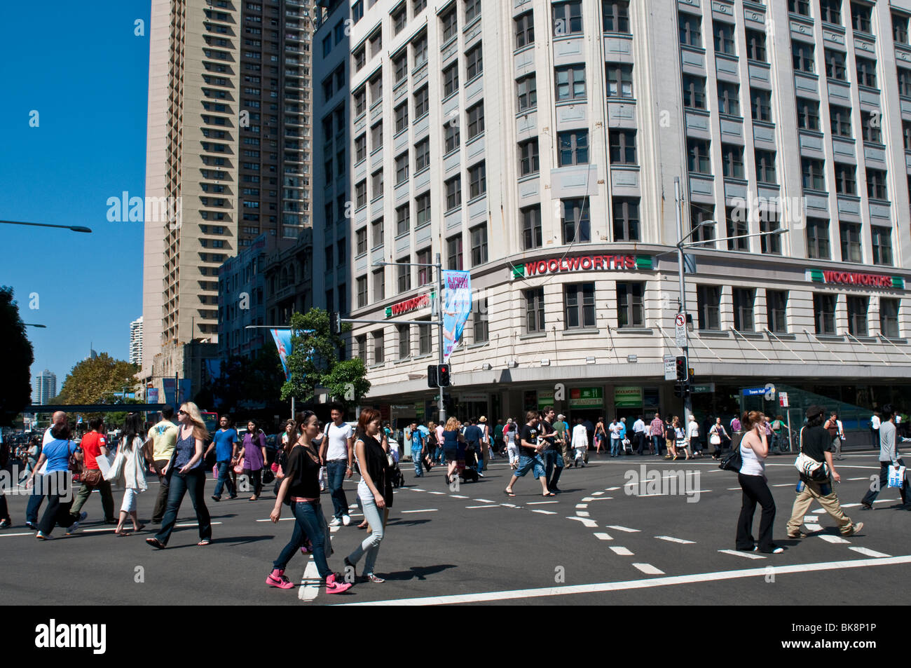 People diagonally crossing George Street at Woolworths supermarket, CBD, Sydney, Australia - Stock Image